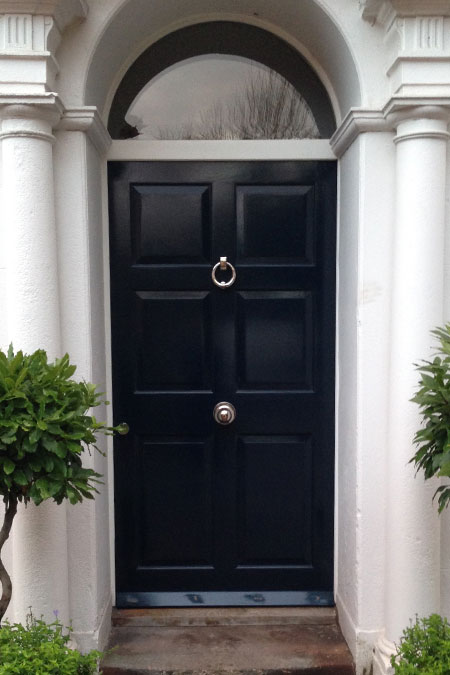 External door painted black with brass furniture